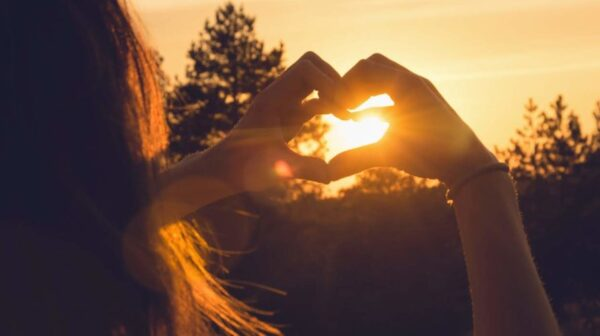 Woman makes heart with hands in sunset. Healthy people  lifestyle. Woman makes heart with hands. Nature lifestyle. Health. Lifestyle. Concept of healthy lifestyle. Happy people. Healthy people. Happiness concept. Young people.